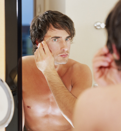 Young man plucking eyebrow, reflection in mirror